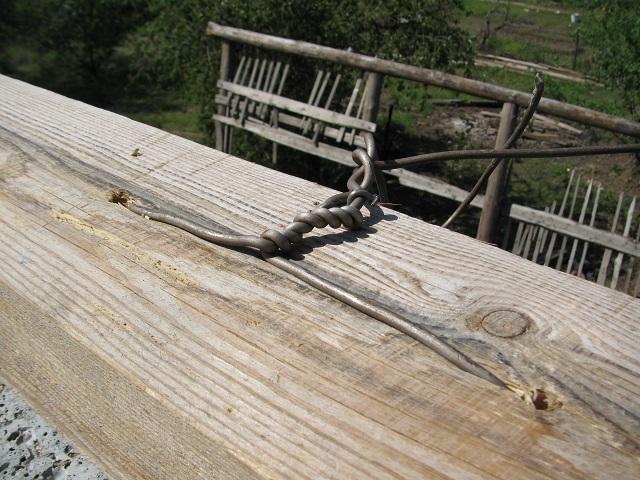 Закрепление мауэрлата скруткой проволоки, пропущенной через просверленные в брусе отверстия.